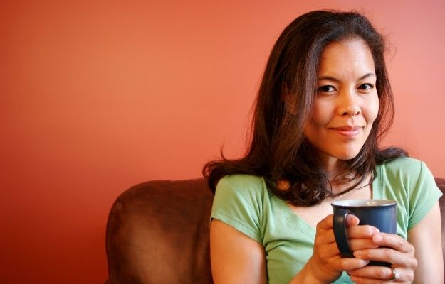 a woman sits on sofa and holds a cup of water   How To Make Your Voice Deeper   Drink Warm Beverages