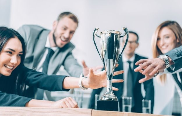 businesspeople trying to catch champion cup | Being No. 1 | 5 Misconceptions About Success That Were Disproven by Coronavirus