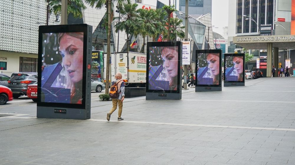 woman walking near the digital advertising boards | Feature | Brand Building 101: How To Build A Better Brand
