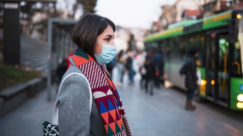 young woman wearing mask standing at the bus stop | Feature | 5 Misconceptions About Success That Were Disproven by Coronavirus