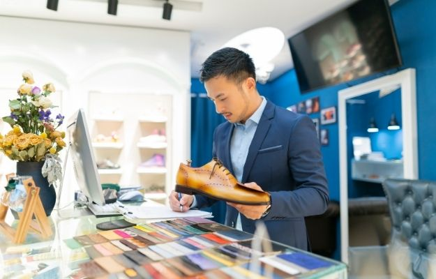 a business man is holding a shoe and writing down the statistic - ca | Entrepreneur Advice Aspiring Business Owners Need to Read | Do Something You Love