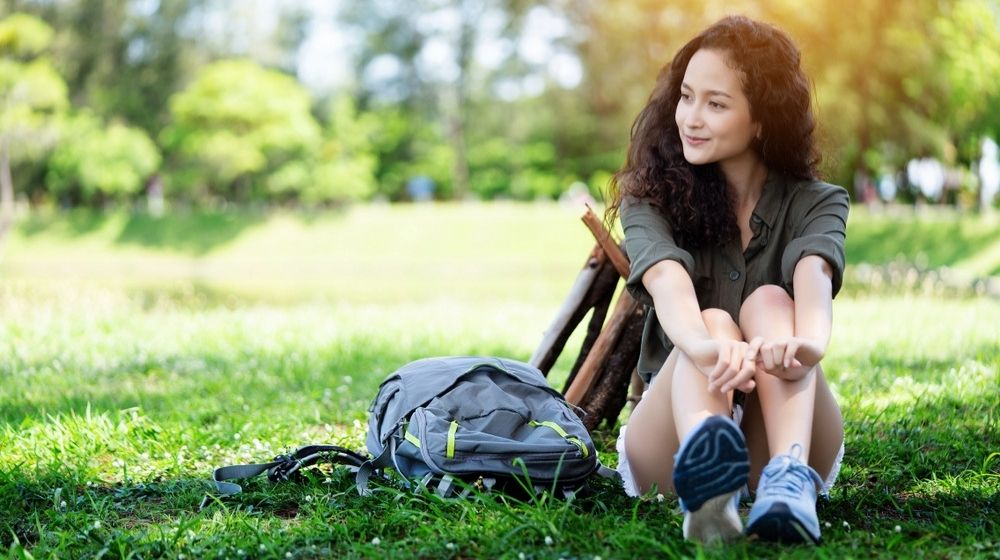 a happy girl sitting in the grass - ss - featured photo   How To Be Better, Not Bitter (In 9 Ways)