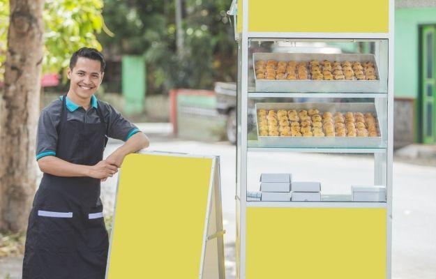 a man is standing next to the food cart | The 8 Types of Entrepreneurship | Adoptive Entrepreneurship