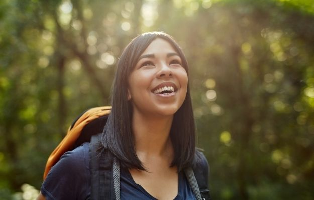a woman is smiling in the jungle   How To Be Stoic In The Face of Challenges   Get Into Nature