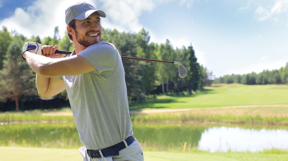 male golfer holding golf club and smiling-feature-ss | How to Be Better At Golf: 5 Easy Ways