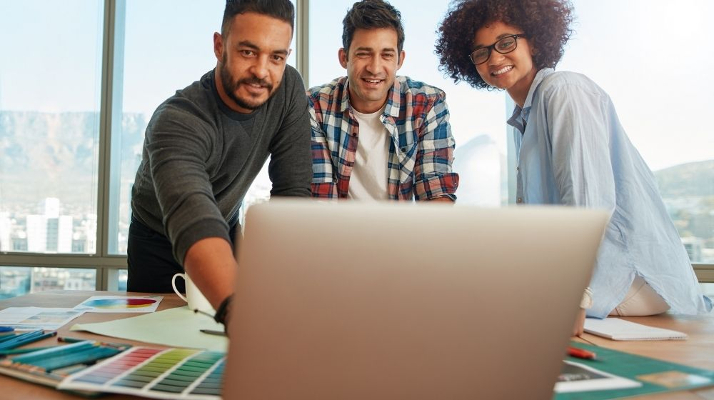 three people are happily looking at the laptop - ca - featured photo | OPB~The 8 Types of Entrepreneurship