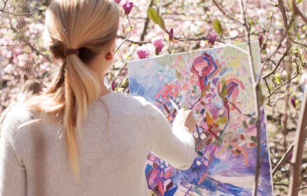 woman in white long sleeve shirt holding white and blue floral painting-us | How To Be A Better Artist | Choose a Favorite Subject