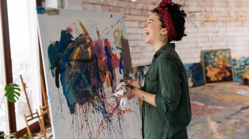 woman with dark curly hair happily laughing and drawing picture by hands with bright oil paints-feature-ss