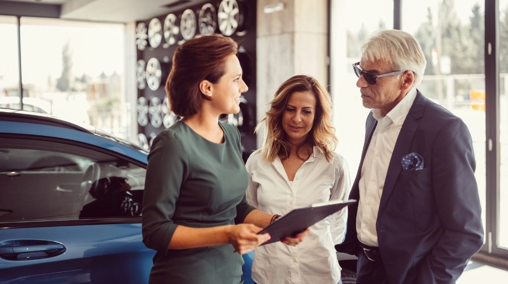 3 people are talking together with the car behind - feature - ca | 5 Tips How To Negotiate A Car Price