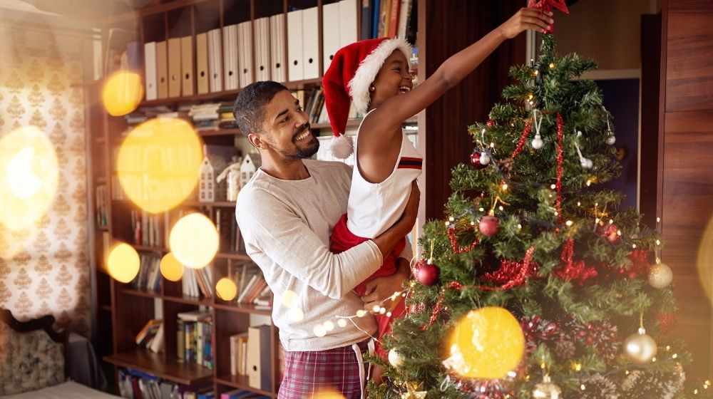 Cute African American girl decorating Christmas tree with smiling father - ss - featured photo | 7 Christmas Tree Decoration Ideas | feature