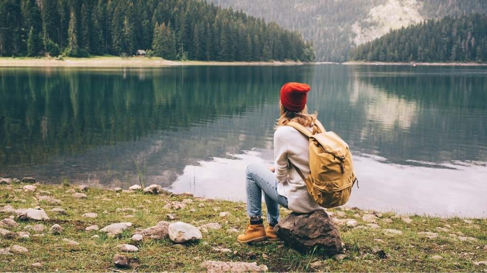 Girl is sitting ont the rock beside the river-feature image-ca | 5 Ways How To Become A Minimalist And Optimize Your Life | feature