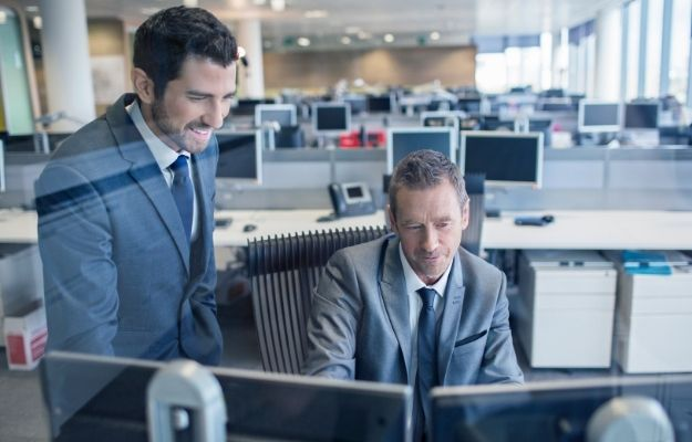 Smilling guy in suit next a senior colleague-ca | How To Impress Your Boss Without Actually Working Harder | Don't Leave Before Your Boss