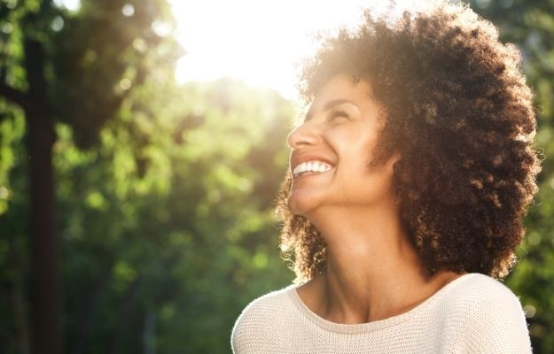 Smilling woman in the sun with a bunch of trees in the background-ca | 5 Ways How To Become A Minimalist And Optimize Your Life | Gain More Self-Confidence
