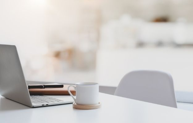 White and clean workspace with laptop and a mug-ca | How To Impress Your Boss Without Actually Working Harder | Have a Clean, Well-Organized Workplace