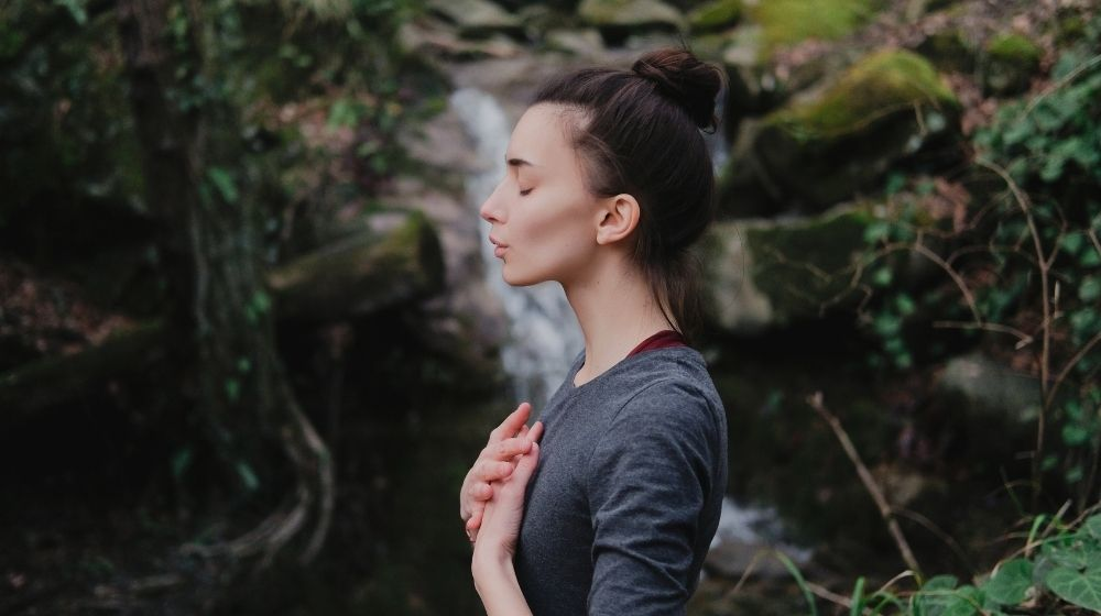 Young woman practicing breathing yoga outdoors in moss forest on waterfall background-feature-ss | How To Breathe Better For Better Focus and Overall Health