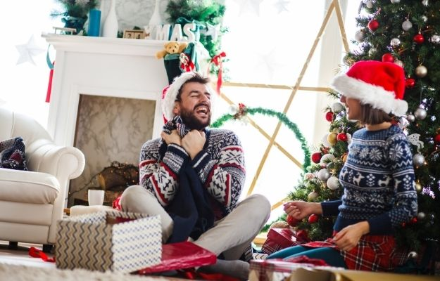 a couple is unboxing next to christmas tree -ca   5 Christmas Shopping Tips In The Age of COVID   Make a Shopping List and a Budget