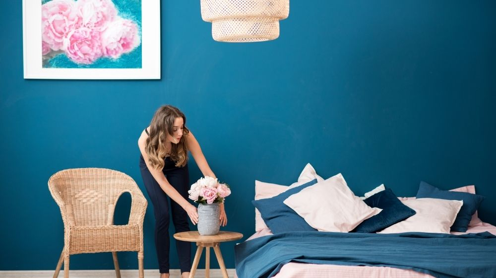 a girl is put a vase on a pedestal next to a bed - feature - ca | How to Decorate Your Room Like A Pro - 7 Ways | feature