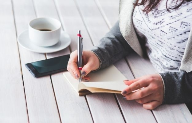 a girl is writing down on notebook with phone and a cup of coffee on the table - ca