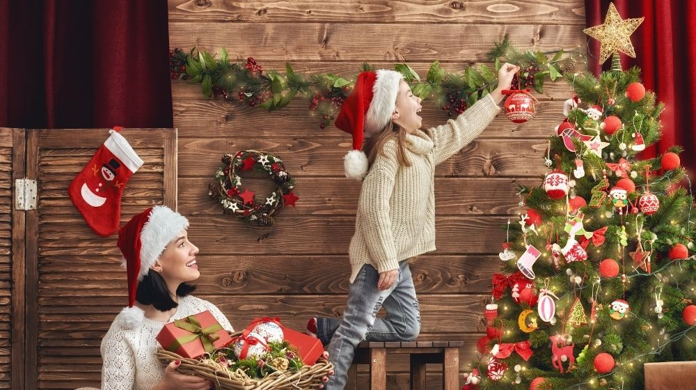 a kid and a woman is decorating christmas tree -feature -ca | Christmas Party Games That Will Keep You Entertained For Hours | feature