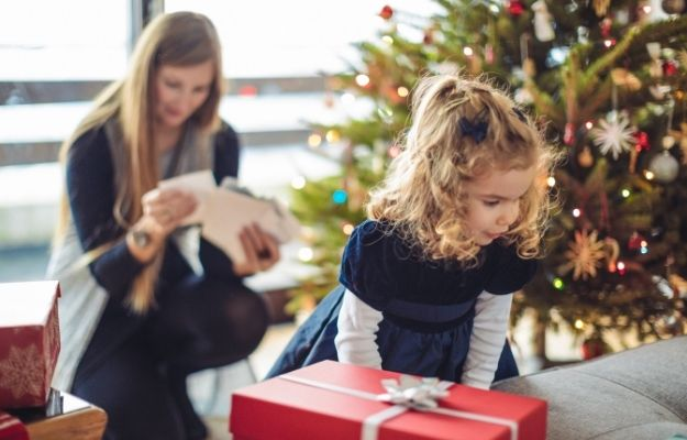 a kid and a woman is having fun beside the christmas tree -ca | Christmas Party Games That Will Keep You Entertained For Hours | Guest the Gift