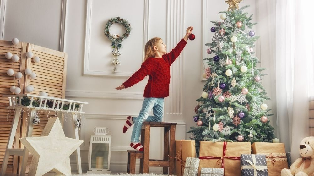 a kid is holding ornament - feature - CA | 5 Christmas Shopping Tips In The Age of COVID | Feature