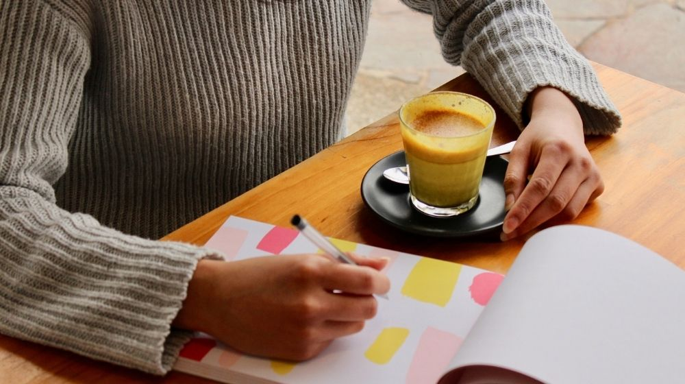 a man writing down on colorful notebook and a cup of coffee on the table - us - featured photo | How To Write A GOOD How-To Guide