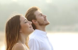 couple of man and woman breathing deep fresh air together at sunset-ca | How To Breathe Better For Better Focus and Overall Health| Breathing Methods