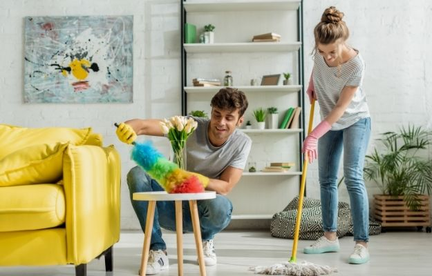 happy man and woman doing spring cleaning in apartment-ss | 5 Ways How To Become A Minimalist And Optimize Your Life | Clarify Your Mind