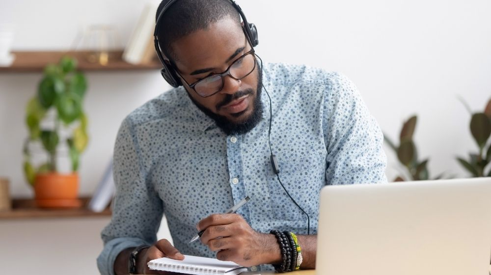 Focused african man in headphones writing notes in notebook watching webinar video course | feature | Top 8 Useful Skills To Learn