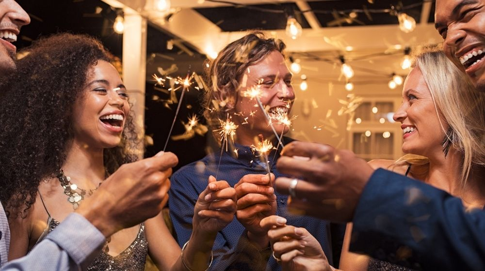 People smiling while holding wine glass and sparkler - New Year Resolutions Quotes - CA | 13 Best Inspiring NYE Quotes for 2021 | New Year's Resolutions Quotes