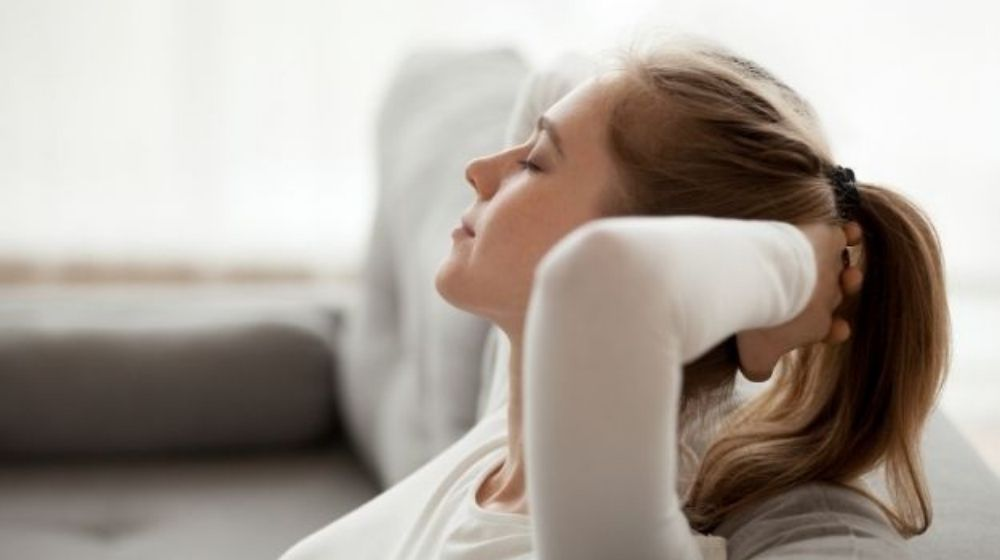 a girl sitting on sofa, relax and put her hand behind her head - feature - ca | How To Find Inner Peace | feature