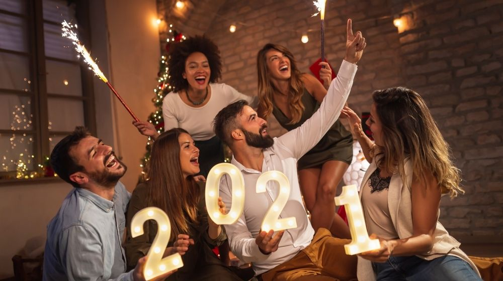 a group of friends is celebrating New Year party - ss - featured photo | 3 Tips For The Best Stay At Home NYE Party | feature