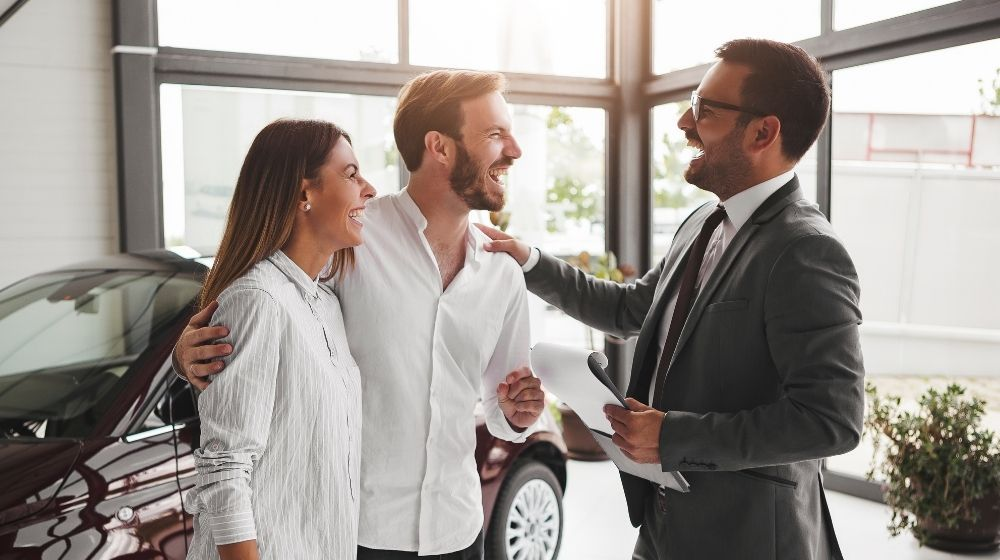 a suited man and a couple are happily talking in a…om with a car on the background - feature - ca | Improve Your Sales Skills With These 7 Tips | feature