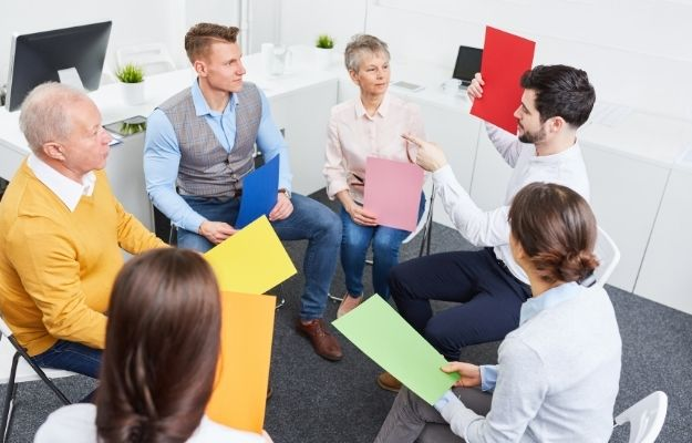 a traing session with 6 people and each one is hodling a a4 paper with different color - ca | Improve Your Sales Skills With These 7 Tips | Attend Workshops and Training Sessions