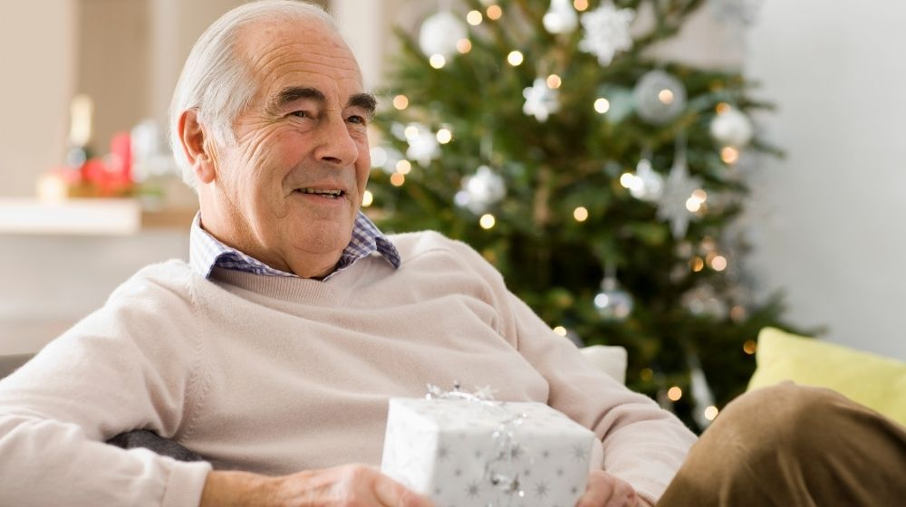 an old man holding the present next to christmas tree -feature - ca | Great Gifts for Dad at Christmas | feature
